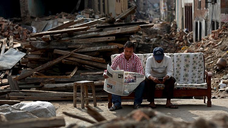 Dos hombres sentados al lado de una vivienda devastada en un suburbio de Katmandú (Nepal) el 15 de mayo de 2015.