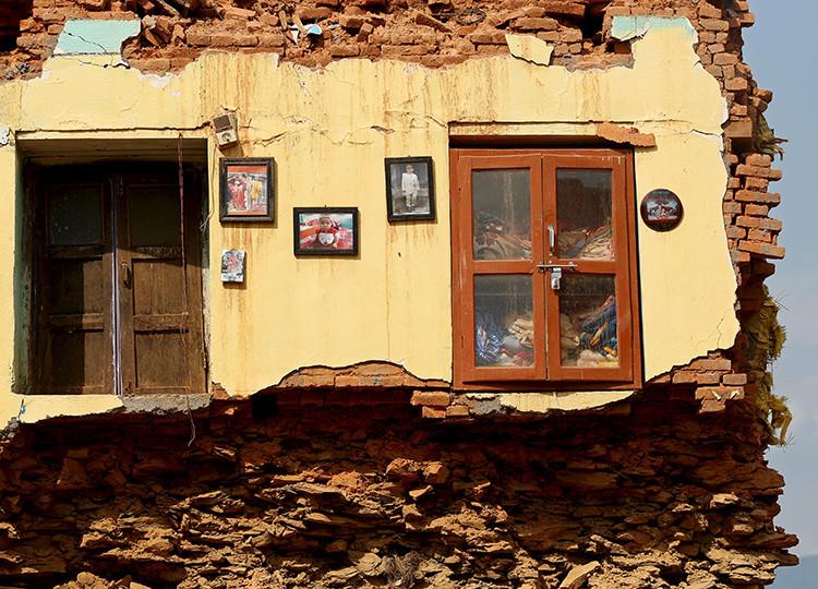 Varias fotos permanecen colgadas de una pared de una vivienda destruida por un sismo en el distrito de Sindhupalchowk (Nepal) el 13 de mayo de 2015.