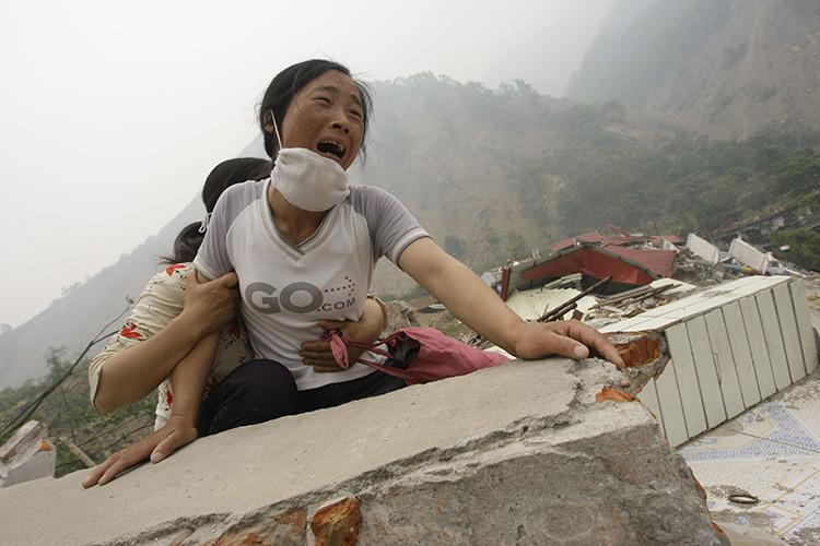 Una mujer llora sobre los escombros de una escuela destruida por un sismo en la provincia de Sichuan (China) el 17 de mayo de 2008.