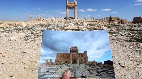 Esta vista general tomada el 31 de marzo de 2016 muestra al fotógrafo sosteniendo una foto del templo de Bel tomada el 14 de marzo de 2014.