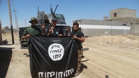 Las fuerzas de seguridad iraquíes con una bandera del Estado Islámico
