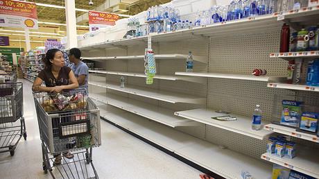 Una compradora pasea entre estanterías vacías mientras busca agua embotellada en un Stop and Shop [un supermercado] en Rockaway Beach, Nueva York, 26 de agosto de 2011.