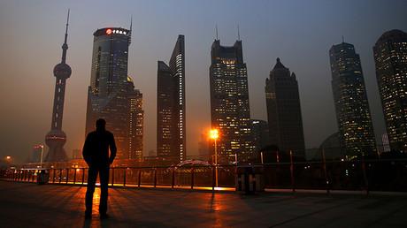 Un hombre dirige su mirada al distrito financiero de Pudong en Shanghái el 20 de noviembre de 2013.