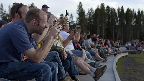 Los espectadores observan la erupción de un géiser en el parque de Yellowstone