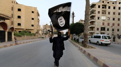 Un miembro del Estado Islámico con una bandera de la organización terrorista en la localidad siria de Raqa el 29 de junio de 2014.