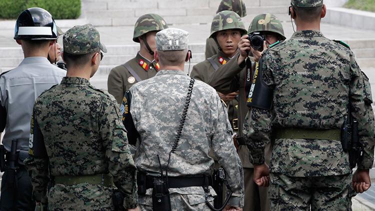 Un soldado de Corea del Norte fotografía a soldados de EE.UU. y de Corea del Sur que hacen guardia después de una ceremonia dedicada al 59.º aniversario de la firma del acuerdo de armisticio que puso fin a la Guerra de Corea, el 27 de julio de 1953. La foto fue tomada el 27 de julio de 2012.