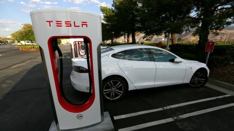 Un vehículo eléctrico Tesla aparcado al lado de un surtidor eléctrico