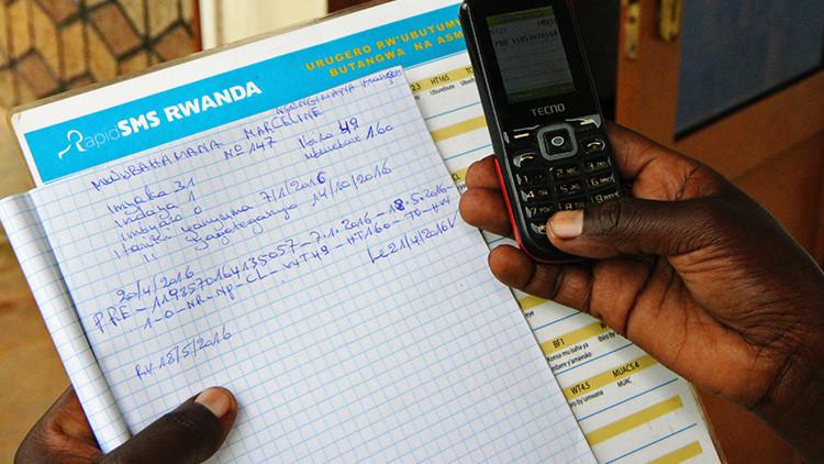 Una mujer embarazada registra su información mediante mensaje de texto en el sistema RapidSMS en Nyarukombe, Ruanda, 27 de abril de 2016.