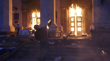Un hombre lanza una bomba incendiaria contra la Casa de los Sindicatos de Odesa, Ucrania. 2 de mayo de 2014.