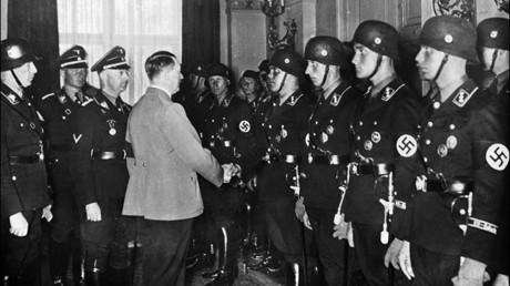 Adolf Hitler saluda a jóvenes miembros de la unidad de élite de las SS nazi en 1937 e,n Berlín, ante la mirada de Heinrich Himmler, el jefe de la Gestapo (la policía secreta del estado nazi).