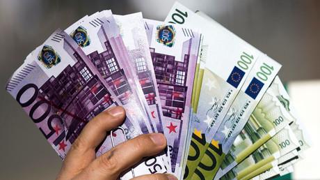 Un activista muestra billetes durante una manifestación frente a la Comisión Europea, Bruselas, 12 de abril de 2016.