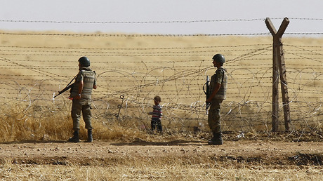 Un niño refugiado sirio está esperando en la frontera entre Turquía y Siria para cruzar a Turquía