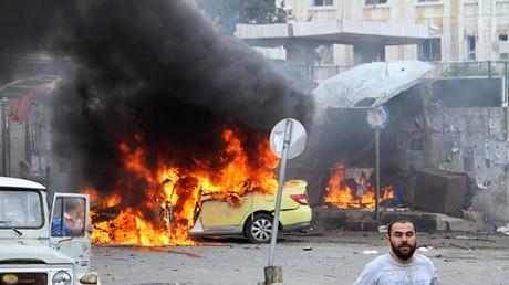 Un soldado del Ejército sirio y civiles inspeccionan los daños tras la serie de explosiones en la ciudad siria de Tartus
