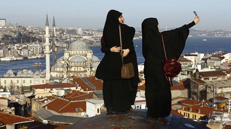 Jóvenes musulmanas se toman una selfie frente a la Mezquita Nueva, cerca del estrecho del río Bósforo, en Estambul