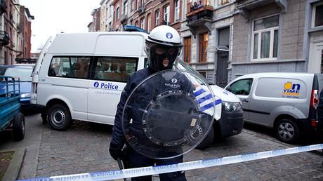 Un policía monta guardia tras fijar un perímetro de seguridad en el barrio de Molenbeek (Bruselas)