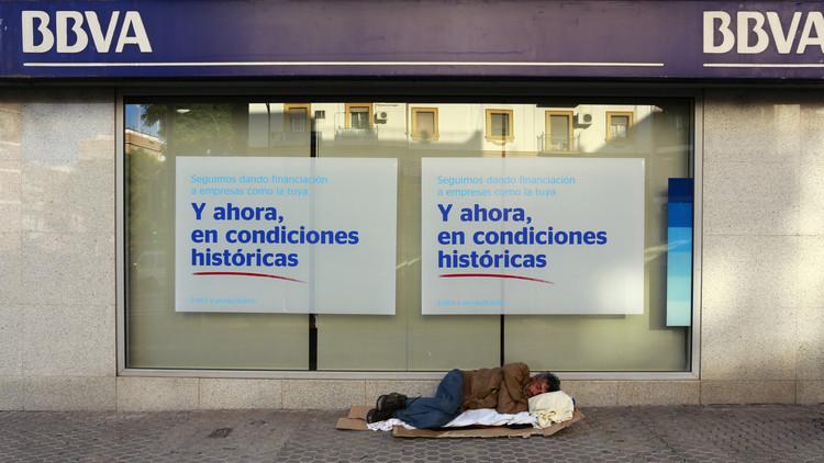 Un hombre sin hogar duerme al lado de una sucursal del BBVA en Sevilla, España, octubre del 2014.