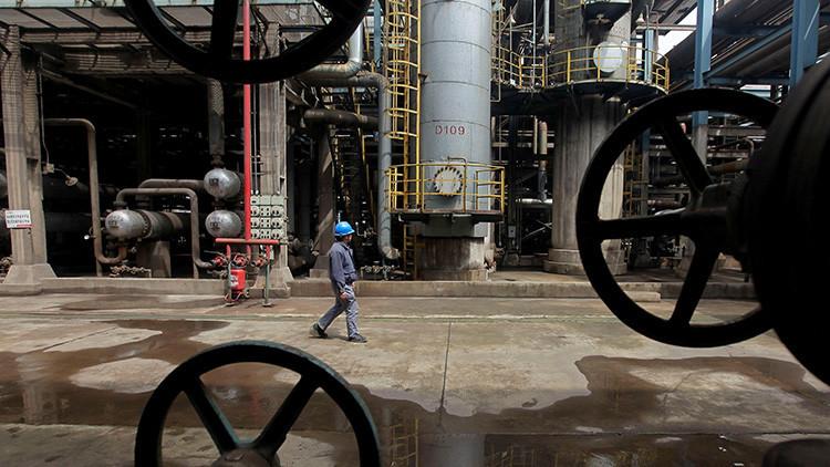 Un trabajador camina entre tuberías de petróleo en una refinería en Wuhan, provincia de Hubei, China, 23 de marzo de 2012.