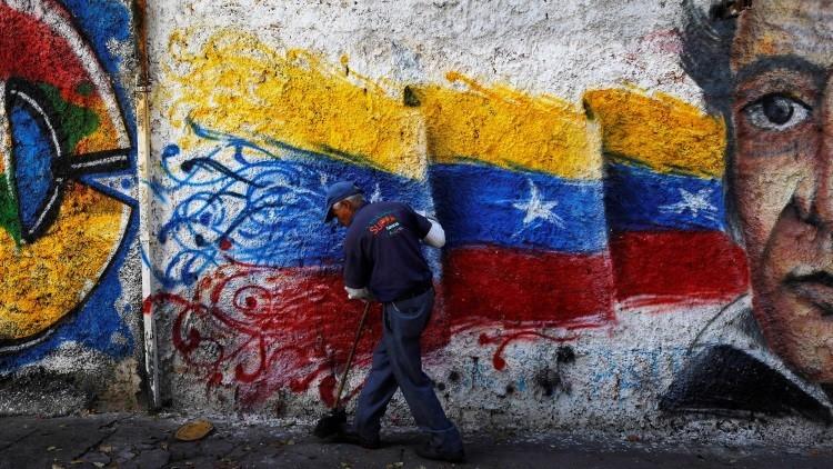 Un barrendero limpia la calle junto a una pintura con los colores de la bandera venezolana, Caracas, Venezuela, el 8 de junio de 2016.