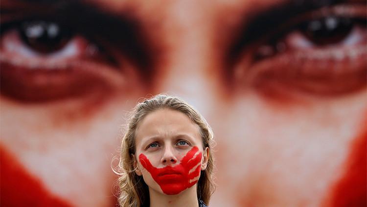 Una activista posa frente a una foto del fotógrafo brasileño Marcio Freitas durante una protesta organizada por la organización no gubernamental Río de Paz contra la violencia hacia las mujeres en la playa de Copacabana, Río de Janeiro, Brasil, el 6 de junio de 2016.