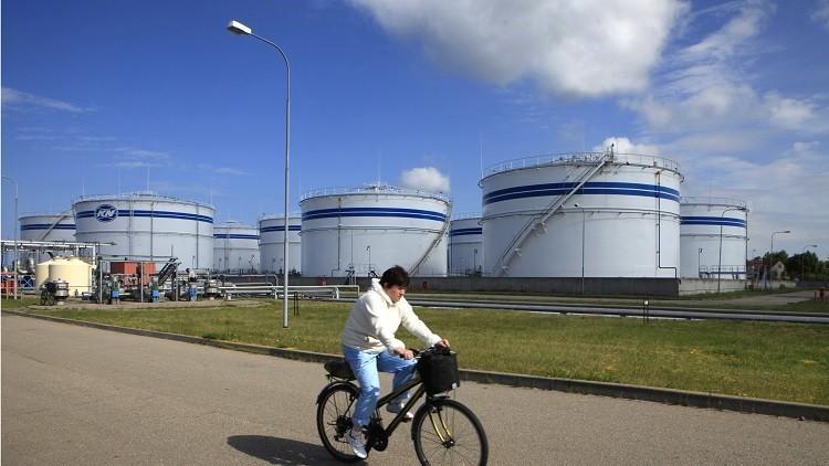 Una mujer en una bicicleta pasa cerca de los contenedores de petróleo en el puerto de la ciudad de Klaipeda