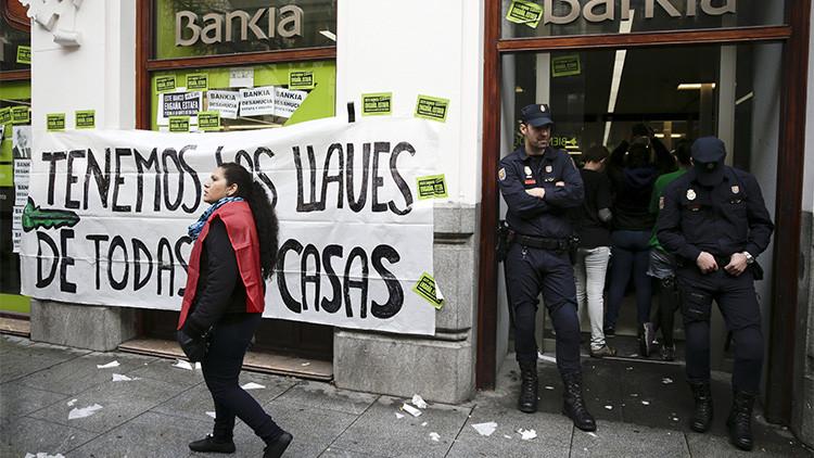 Una activista anti-desalojos pasa ante una pancarta mientras que unos policías bloquean la entrada de una sucursal bancaria de Bankia durante una protesta contra los desalojos en Madrid, España, el 11 de febrero de 2016.