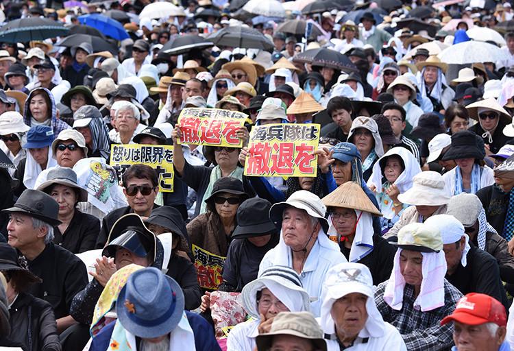 """Manifestantes llevan pancartas con la inscripción """"¡Fuera marines!"""" durante una protesta contra la presencia militar estadounidense en Okinawa, Naha, Japón, el 19 de junio de 2016."""