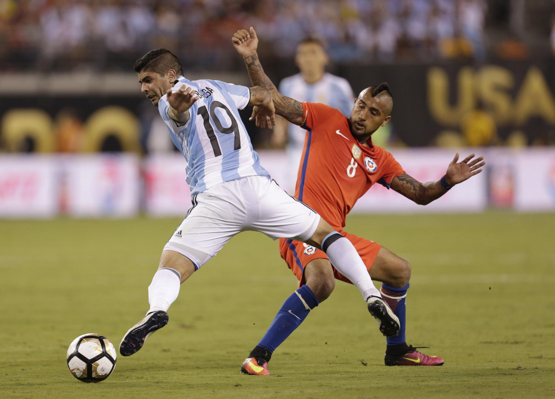 El Argentino Ever Banega disputa un balón con el chileno Arturo Vidal