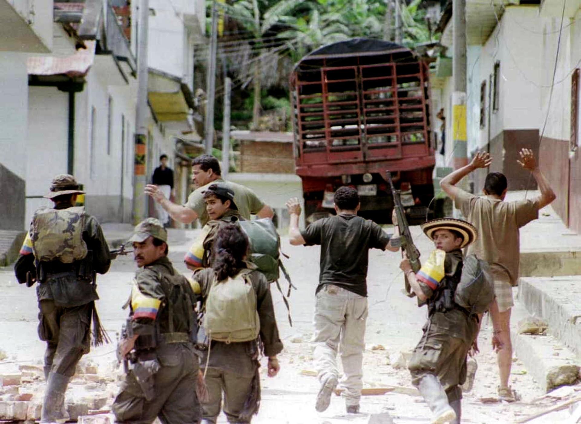Miembros de las FARC toman como rehenes a tres policías que fueron capturados durante un ataque en la ciudad de Dolores (Colombia) en noviembre de 19