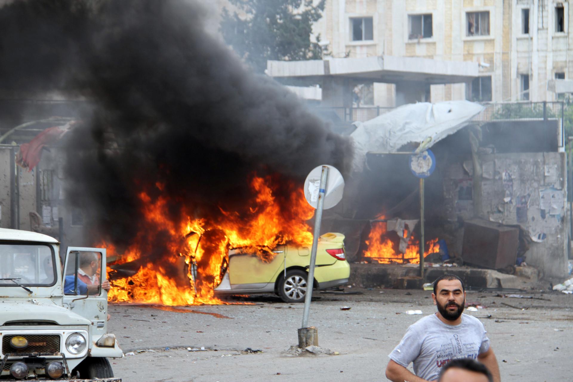Varias personas examinan los daños que causaron unas explosiones en Tartús, Siria.