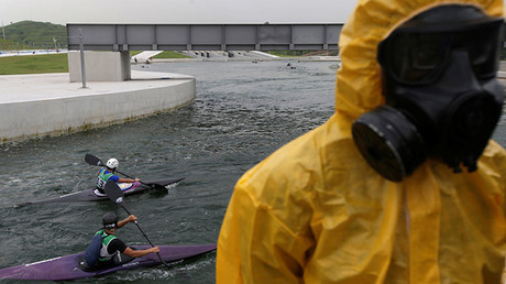 Atletas entrenan en canoa mientras soldados brasileños participan en un entrenamiento contra presuntos ataques químicos, biológicos, radiológicos y nucleares antes de los Juegos Olímpicos de Río de Janeiro 2016