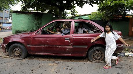 Niños juegan con un auto abandonado en las calles de Asunción, Paraguay
