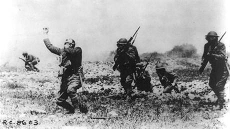 Cinco soldados norteamericanos avanzan con máscaras de gas y otro se lleva la mano a la garganta, Primera Guerra Mundial