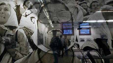 Personas que asisten a una exposición dedicada a las Abuelas de Plaza de Mayo son vistas a través de una foto del fotógrafo argentino Daniel García, 24 de marzo de 2014