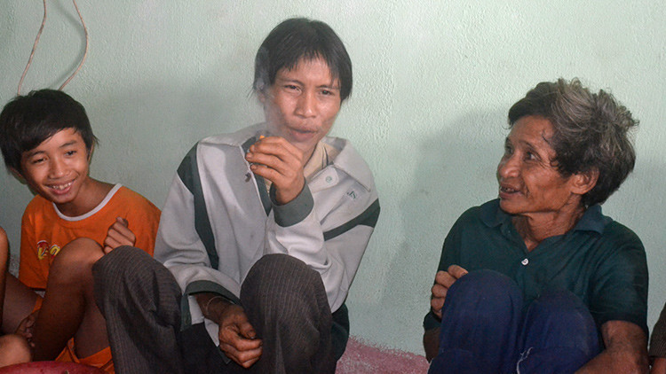 El hijo rescatado, Ho Van Lang, fuma mientras lo cuidan dos habitantes de la aldea de la que huyó con su padre durante la guerra de Vietnam
