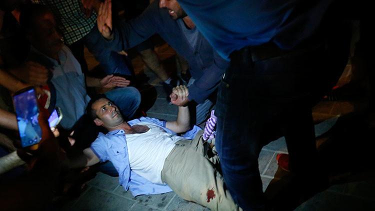 La gente ayuda a un hombre herido cerca de la plaza Taksim, en Estambul, Turquía, el 16 de julio de 2016.