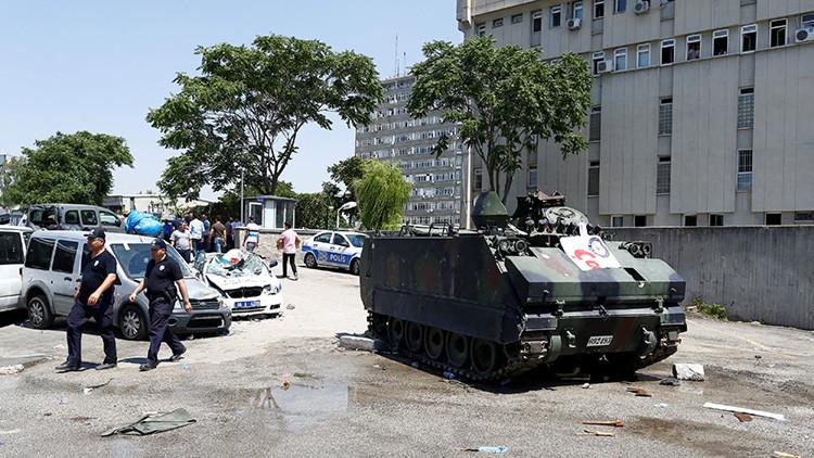 Varios vehículos se observan cerca de un vehículo militar blindado frente a la jefatura de policía de Ankara