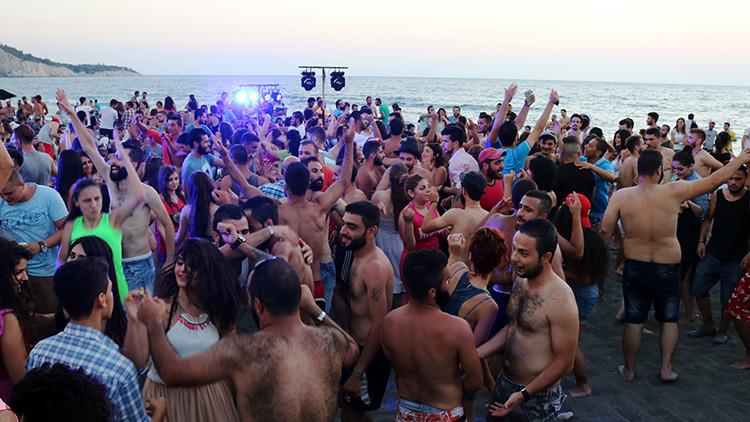 La otra cara de la guerra en Siria: Cientos de jóvenes se relajan, fuman y bailan en la playa