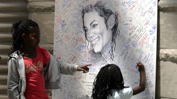 Dos fanáticos de Michael Jackson firman un cartel del cantante en Detroit después de su funeral.  7 de julio de 2009.