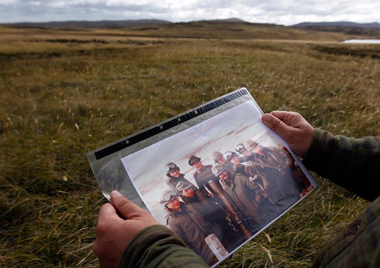 Jorge Bratulich, veterano de la Guerra de las Malvinas, sostiene una imagen en la que aparece con otros soldados cerca de la ciudad Puerto Argentino, Islas Malvinas, 2 de marzo de 2012.