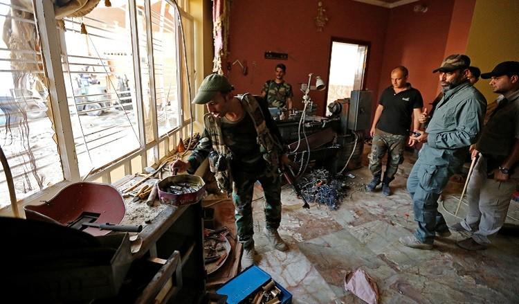 Miembros de la Organización chiíta Badr inspeccionan una fábrica que había estado ocupada por militantes del Estado Islámico, en Faluya.