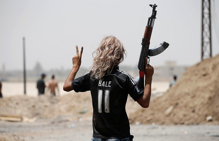 Un peculiar miembro de las fuerzas estatales hace la señal de la victoria en medio de las ruinas de la urbe.