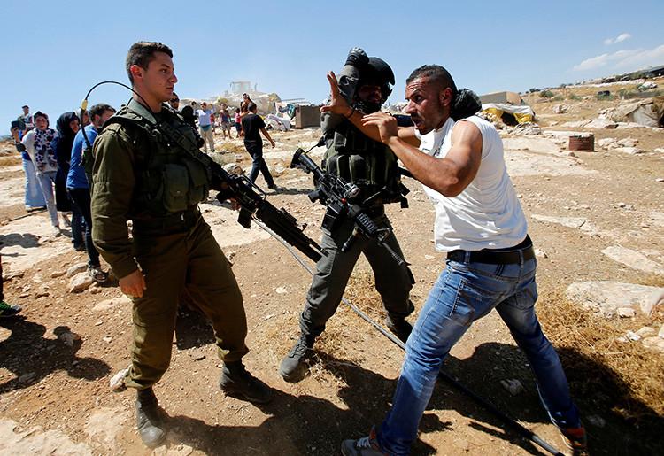 Un policía israelí de fronteras detiene a un palestino cerca de la localidad cisjordana de Yatta, al sur de Hebrón, el 19 de de junio de 2016.