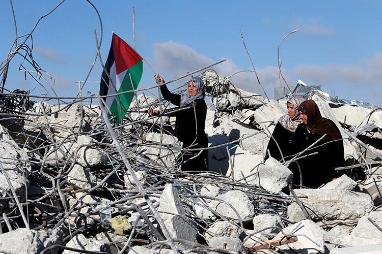La madre del agresor palestino Murad Idais sostiene una bandera palestina en los escombros de su casa demolida por las fuerzas israelíes en la localidad cisjordana de Yatta, al sur de Hebrón, el 11 de junio de 2016.