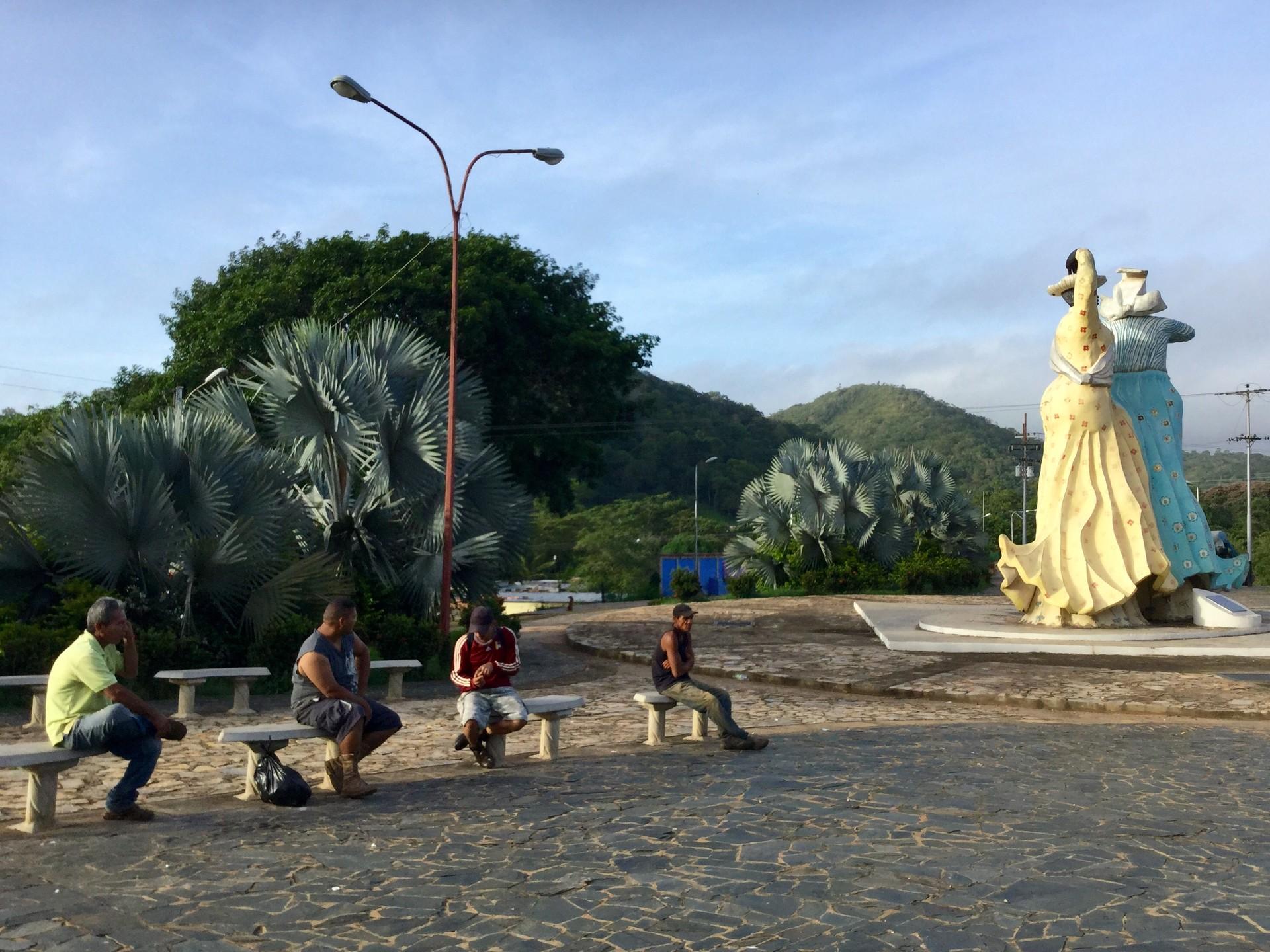 Los trabajadores de la minería esperan a las afueras de El Callao la llegada de un camión que los traslade a las minas.