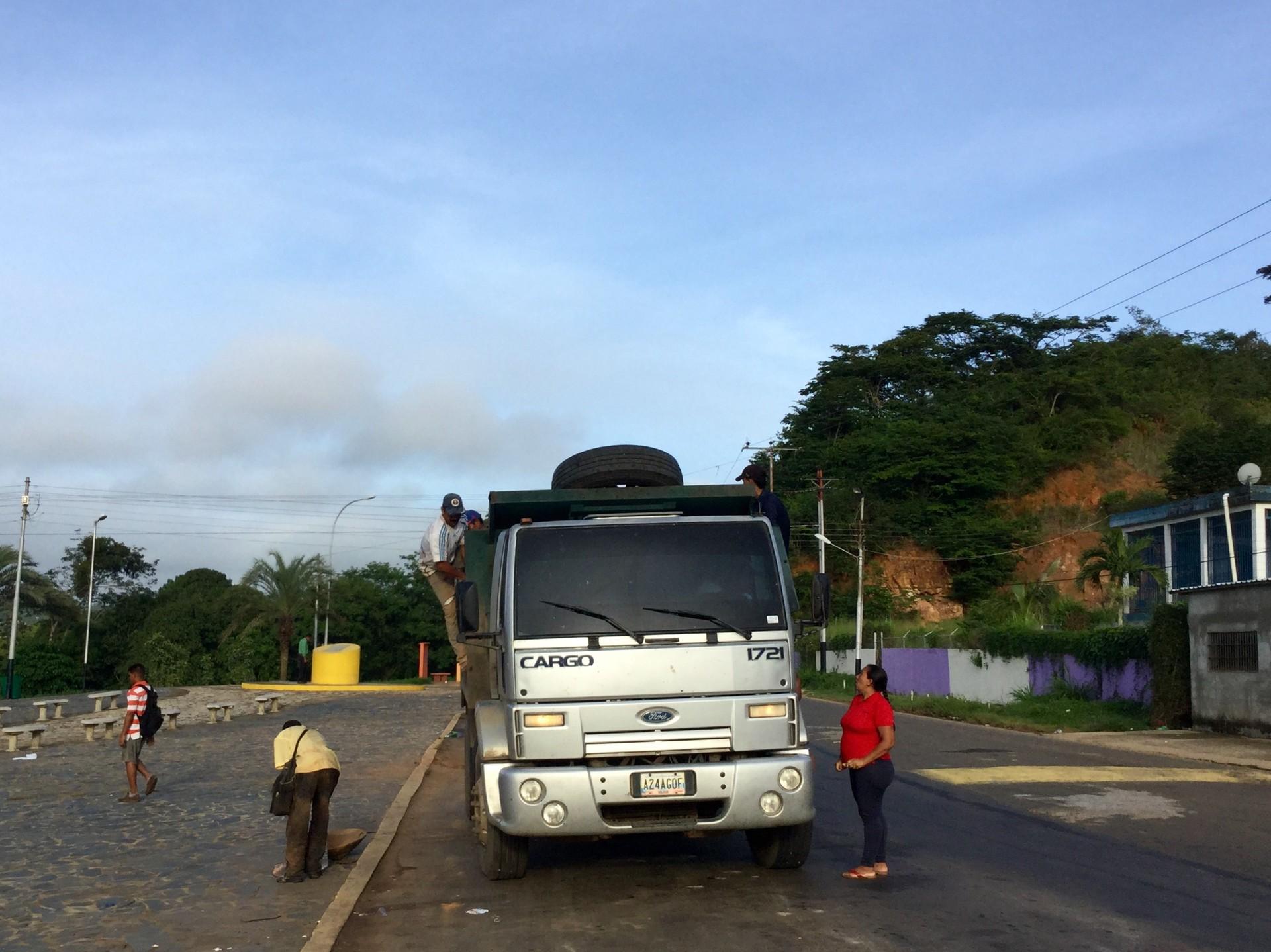 Un camión se apuesta en la entrada del pueblo a dejar mineros y recoger a otros que emprenden su viaje a los yacimientos de oro de la zona.