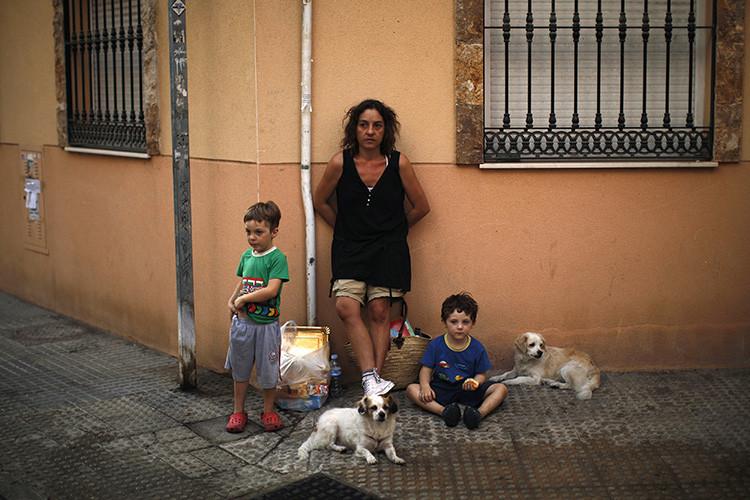 Carolina González, de 39 años, con sus hijos de tres y cuatro años en una calle tras ser desalojados por la policía de un edificio abandonado en Málaga