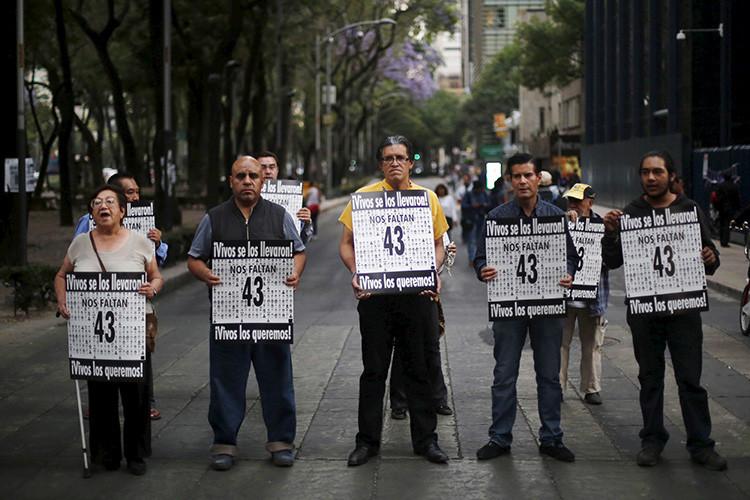 Activistas sostienen pancartas para exigir justicia por los 43 estudiantes desaparecidos frente a la oficina del procurador general de México en la Ciudad de México