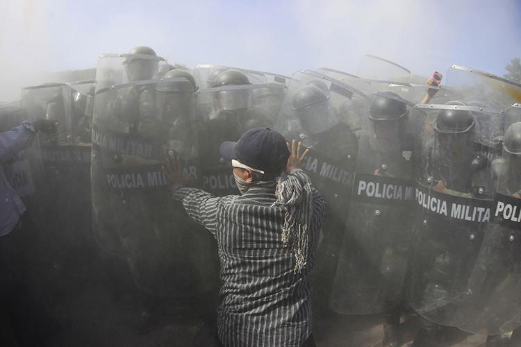 Un pariente de uno de los 43 estudiantes desparecidos en Ayotzinapa se enfrenta a agentes de la Policía Militar durante una manifestación en Iguala