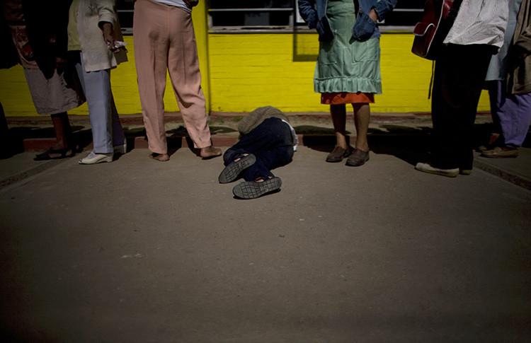 Una mujer se encuentra en el suelo mientras otros esperan en la cola para conseguir comida en el refugio Villa Mujeres en Ciudad de México.