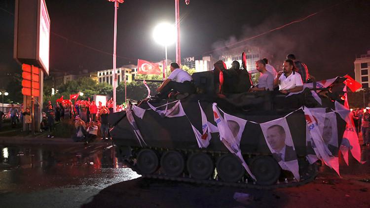 Partidarios del Gobierno turco sentados en un vehículo blindado decorado con retratos del presidente Erdogan en Ankara, Turquía, el 16 de de julio de 2016.
